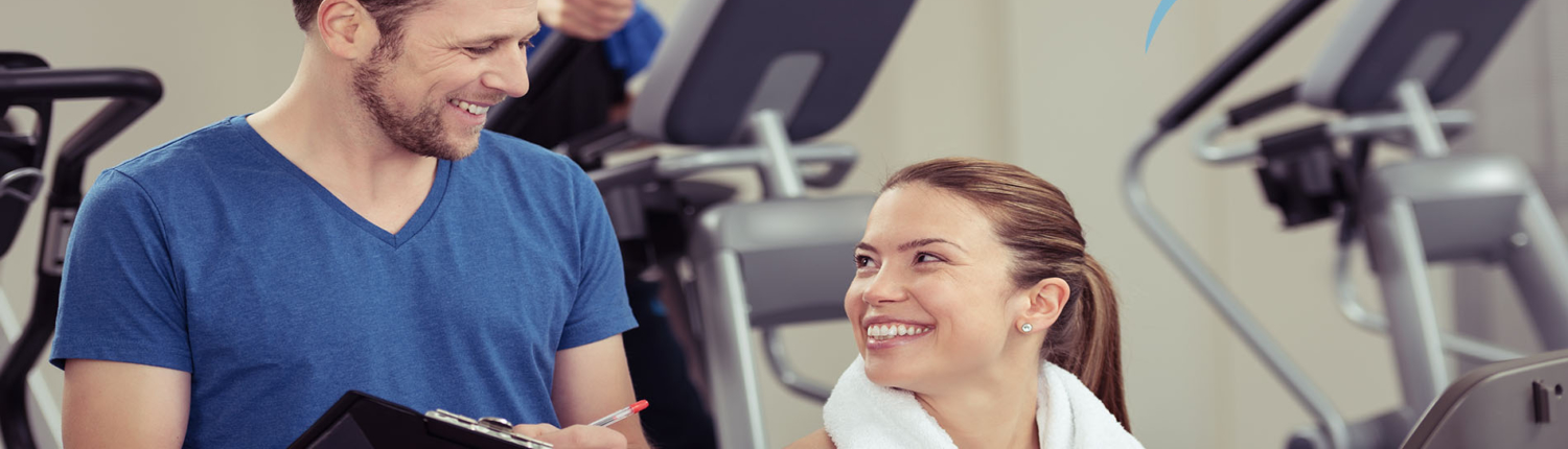 Smiling fitness instructor in blue shirt stands beside woman sitting on a fitness machine
