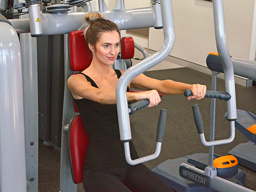 smiling woman dressed in black sitting on gym equipment