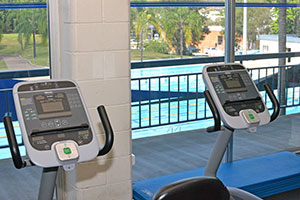 walking machines in gym overlooking outdoor pool