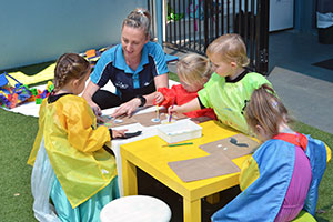 children and carer paint together around a table
