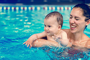smiling woman and baby swimming in pool