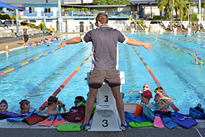 swimming instructor stands at end of pool and instructs swimming students