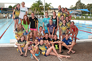 Members of swim club stand beside pool in a group