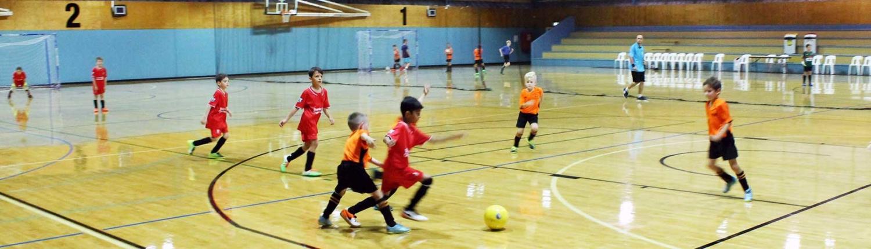 Children play Futsal on indoor basketball court
