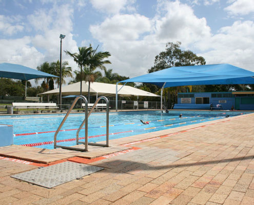 outdoor swimming pool with swimmers doing laps