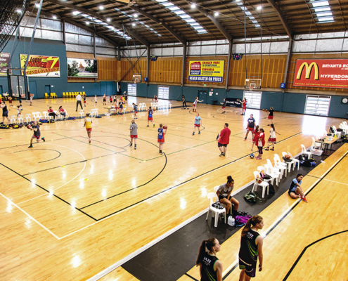 basketball court with players running and playing a game of basketball