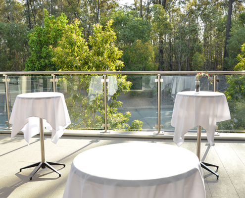 Cocktail tables with white table clothes on empty balcony