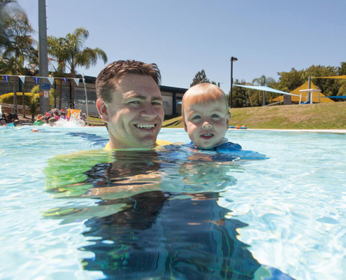 Smiling man holds toddler in swimming pool