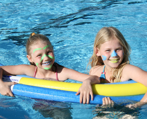 two smiling children in pool floating on pool noodles