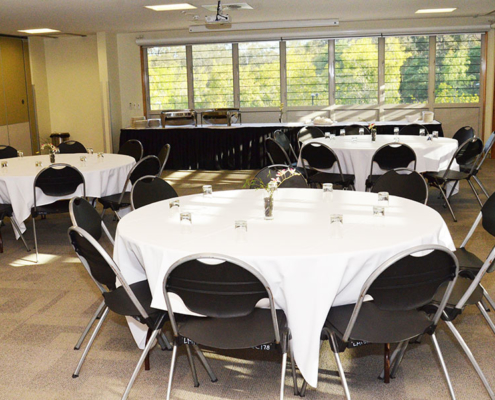 Round tables with white table cloth and black chairs set up to seat 8 people