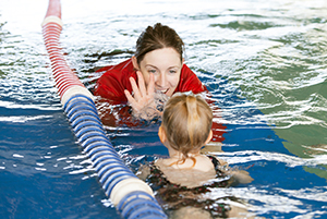 woman teaching child to swim