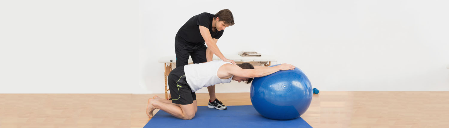 man does exercise using exercise ball while trainer assists