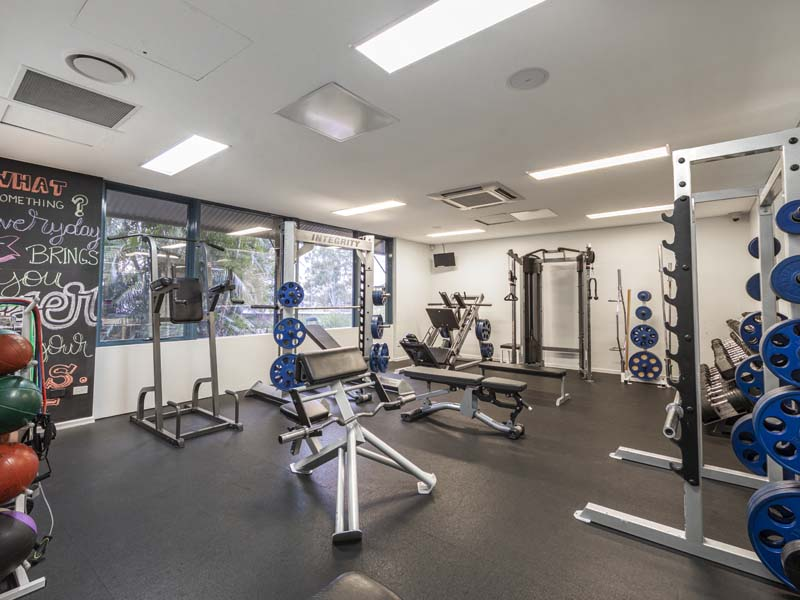 gym free weights room with various weight machines and weights situated throughout the room