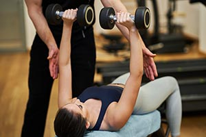 Woman laying on gym bench holds weights above her body