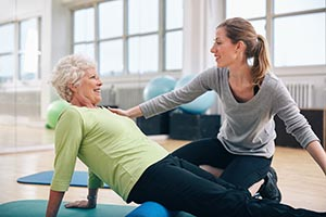 Older woman doing stretches while gym instructor supports her