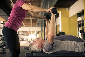 Man laying on his back holding gym weights above his body, a woman stands nearby