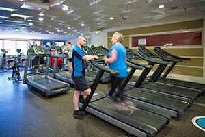 Woman runs on gym running machine as gym instructor watches on