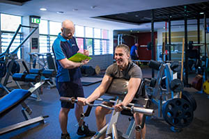 man works out as gym instructor looks on