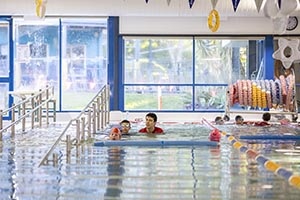 Logan indoor pool with adult and child swimming at one end
